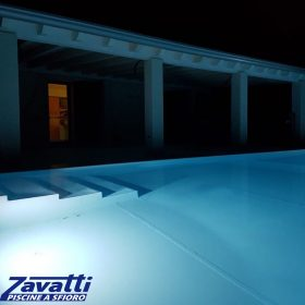 Close up piscina a sfioro senza vasca di compenso. Rivestimento grigio messo in risalto dall'illuminazione a LED a basso consumo energetico