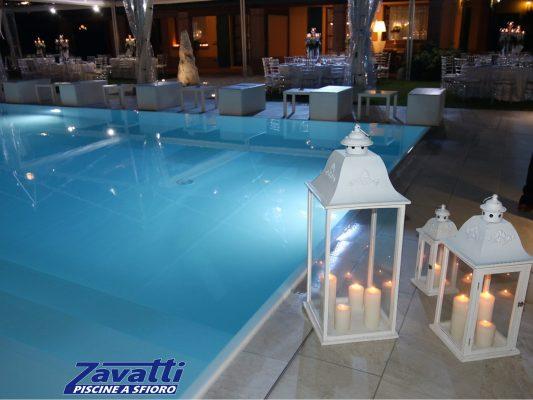 Vista notturna di una piscina a sfioro Zavatti illuminata da lampade LED e lanterne