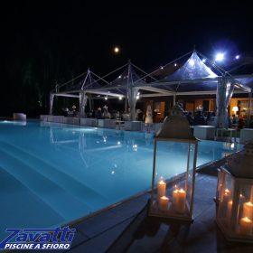Cena a bordo di una piscina a sfioro Zavatti con rivestimento bianco