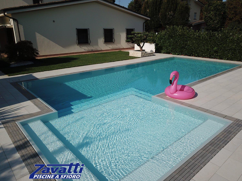 Primo piano bagnasciuga di una piscina Zavatti. L'ampia spiaggia è l'elemento principale di design della realizzazione