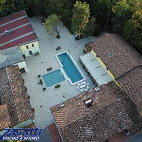 Vista da drone di una piscina a sfioro Zavatti con liner ad alta pigmentazione grigio scuro