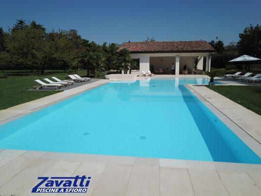 Vista frontale piscina a sfioro con rivestimento in PVC armato bianco. Il rivestimento utilizzato da Zavatti è anticalcare e resistente ai raggi UV per garantire durevolezza nel tempo