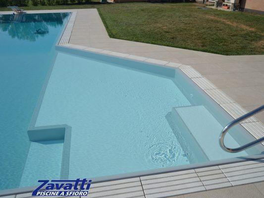 Zona relax piscina a sfioro realizzata con liner grigio. Particolare design dovuto alla forma della piscina e agli scalini bianchi